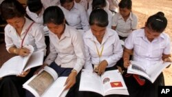 """Cambodian students read a newly-delivered copy of """"A History of Democratic Kampuchea"""" in Anlong Veng, in Uddor Mean Chey province, about 300 kilometers (185 miles) north of Phnom Penh, Cambodia, Monday, June 21, 2010. Cambodian students in the former Khmer Rouge stronghold were issued the textbook Monday that for the first time teaches the atrocities of the past, a little more than a decade after government forces captured the movement's last bastion. (AP Photo/Heng Sinith)"""