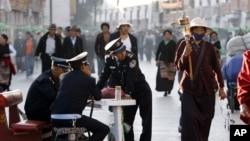 一名藏族小贩走过拉萨街头的中国警察身边走过