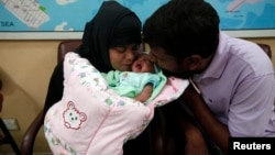 A childless couple kisses their newly adopted daughter, Fatima, whom Pakistani television talk show host Aamir Liaquat Hussain gave them on his show, as they sit at the Chhipa Welfare Association office in Karachi, Aug. 1, 2013.