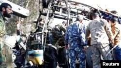 Para anggota pasukan keamanan Suriah memeriksa bangkai bus yang terkena ledakan bom di Damaskus (1/2). (Reuters/Omar Sanadiki)