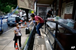 """In this June 11, 2020, photo Lourdes Sherby, center, with Guadalupe Family Services, hands diapers to Louisa Peralta in Camden, N.J. """"I think we're received a lot better than we used to be,"""" said Sgt. Dekel Levy, 41, as he helped hand out diapers."""
