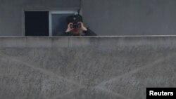 2017年4月15日,中朝两国界河鸭绿江朝鲜一侧新义州的朝鲜士兵在用望远镜观察边境.