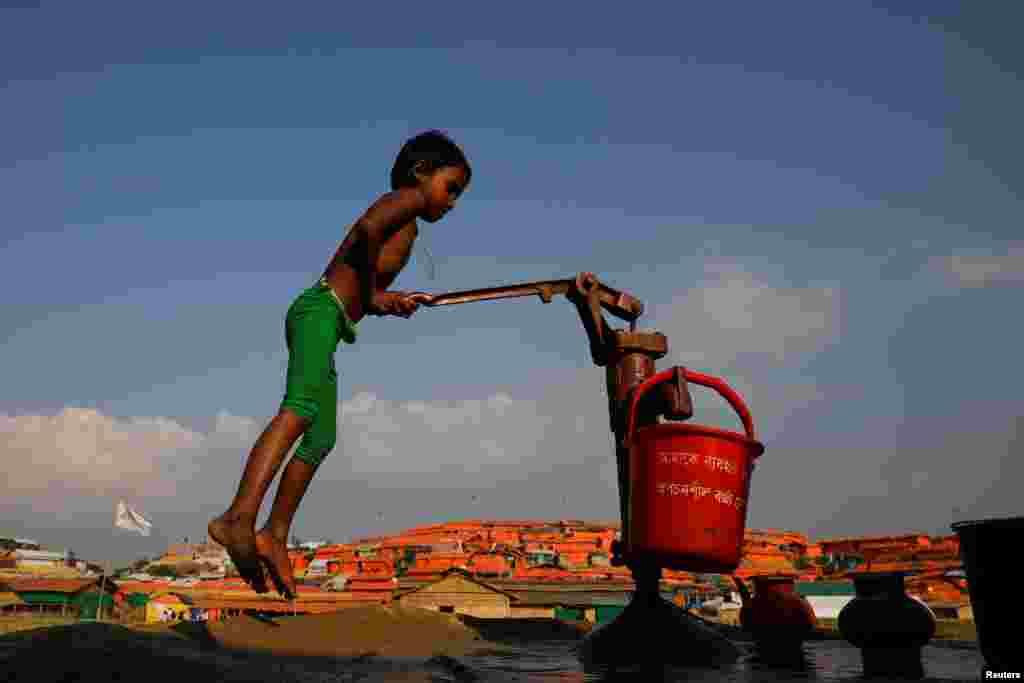 پسر بچه آواره روهینگیایی مشغول پر کردن سطل آب در اردوگاه پناهندگان در بنگلادش است.
