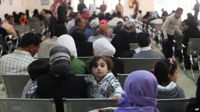 FILE - Syrian refugee families wait to be registered with the UNHCR services, during the Australian Foreign Minister Julie Bishop's visit to the compound, to meet with the UNHCR representative to Jordan, Andrew Harper, regarding the Syrian refugee situation, in Amman, Jordan, April 21, 2014.