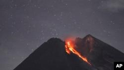 Gunung Merapi terlihat dari Cangkringan, Yogyakarta sedang memuntahkan material vulkanik, 29 Januari 2019. (Foto: AP)