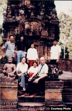 The color photograph of the group includes Richard Dudman (bald), Malcolm Caldwell (flowing hair) and Elizabeth Becker in front of a temple at Angkor Wat. With them are two young aides and Thiounn Prasith, a senior Khmer Rouge official at the Ministry of Foreign Affairs. (Courtesy photo of Elizabeth Becker)