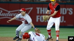 Rep. Raul Ruiz, D-Calif. (L) tags out Rep. Mike Bishop, R-Mich., on the steal attempt with Rep. Tim Ryan, D-Ohio (R), during the Congressional baseball game, June 15, 2017, in Washington.