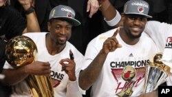 Dvejn Vejd sa trofejem Leri O'Brajen, namenjenom šampionu NBA lige, i Lebron Džejms sa priznanjem za najkorisnijeg igrača finalne serije koji nosi ime Bila Rasela