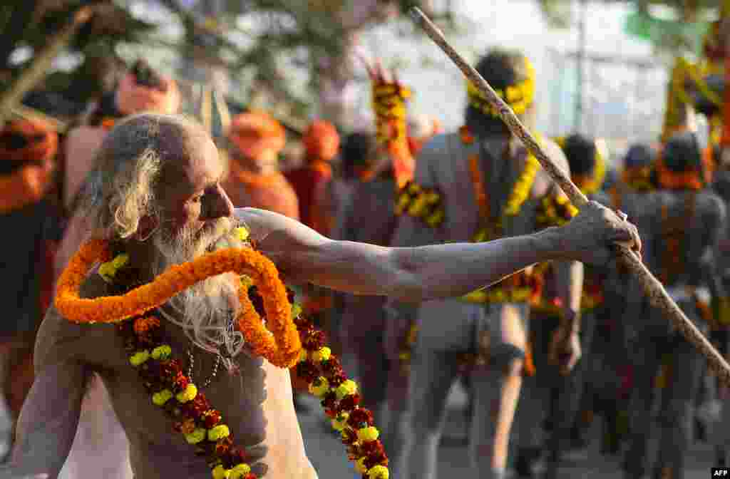 "An Indian elderly naked sadhu (Hindu holy man) takes part in a religious march toward the Sangam area during the ""royal entry"" for the upcoming Kumbh Mela festival in Allahabad."