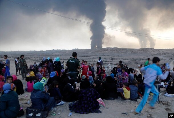 Smoke rises as people flee their homes during clashes between Iraqi security forces and members of the Islamic State group fleeing Mosul, Iraq, Oct. 18, 2016.