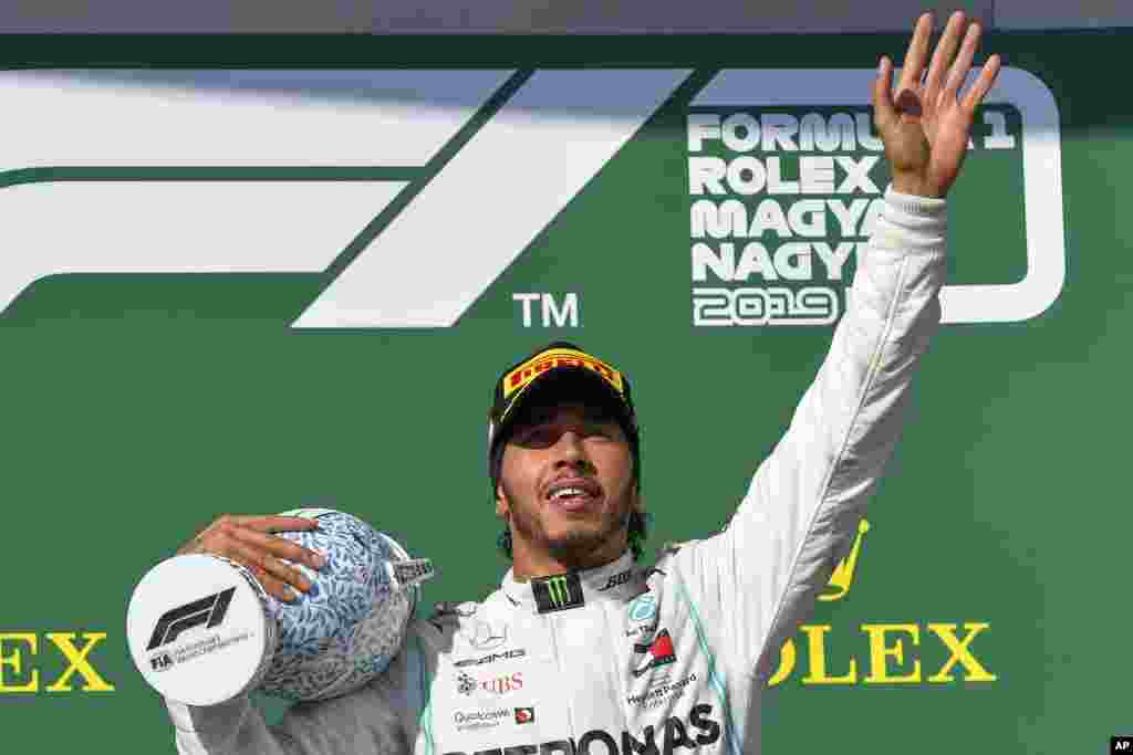 لوئیس همیلتون از تیم مرسدس بنز، قهرمانی در مسابقات اتومبیلرانی فرمول یک در مجارستان را جشن می گیرد.