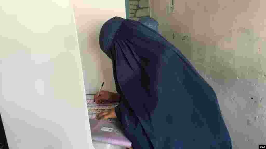 """یک زن رای دهنده حین رای دهی در لیسه """"زرعونه انا"""" در هنگام رای دادن"""