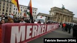 """Biểu tình chống chính sách nhập cư và người nhập cư ở Berlin, ngày 12 tháng 3 năm 2016. Các khẩu hiệu viết rằng """"Bà Merkel phải ra đi""""."""