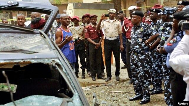 An eye witness of the bomb blast gives his account to the Kano commissioner of the police during the police chief's assessment of the situation in Sabon Gari, Kano, May 19, 2014.