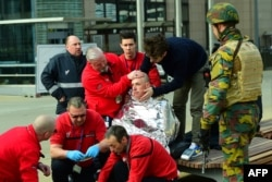 FILE - A victim receives first aid by rescuers, on March 22, 2016 near Maalbeek metro station in Brussels, after a blast at this station near the EU institutions caused deaths and injuries.