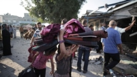 A Palestinian girl carries belongings as she and her family leave the Abu Hussein U.N. school in the Jebaliya refugee camp, northern Gaza Strip, hit by an Israeli strike earlier, July 30, 2014.
