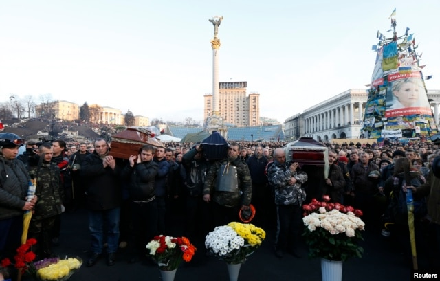 Pallbearers carry the coffins of those killed in Thursday's clashes during a service in Independence Square in Kyiv, Feb. 21, 2014.