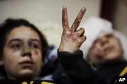 ហាណា (Hana) អាយុ១២ឆ្នាំ លើកដៃធ្វើជាសញ្ញា V (ជ័យជម្នះ) ដាក់បងស្រីនាងអាយុ១៣ឆ្នាំ ខណៈពួកគេកំពុងសម្រាកព្យាបាលរបួសធ្ងន់ ក្រោយពីកងទ័ពស៊ីរី បានបាញ់ផ្លោងដាក់ផ្ទះរបស់ពួកគេនៅក្រុង Idlib ភាគខាងជើងប្រទេសស៊ីរី។ (រូបថតឯកសារ ១០ មី