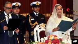 Bangladesh President Abdul Hamid, left, administers the oath to Prime Minister Sheikh Hasina, right, during her swearing in ceremony in Dhaka, Jan. 12, 2013.