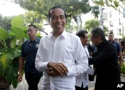 Incumbent Indonesian President Joko Widodo, center, smiles upon arriving for a meeting with leaders of his coalition parties in Jakarta, April 18, 2019.