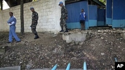 The head of Nepal's mission in Haiti, Lt. Col. Krishna, second from left, and an engineer, left, walk by pipes coming from latrines that lead to septic tanks that crosses a canal that leads to the Artibonite River at Nepal's UN base in Mirebalais, Haiti,