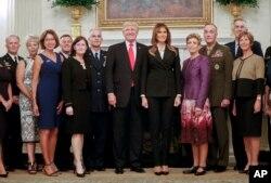 도널드 트럼프(가운데 왼쪽) 미국 대통령과 부인 멜라니아(가운데 오른쪽) 여사가 5일 군 고위 지휘관-배우자 만찬 현장에서 기념촬영을 하고 있다.