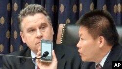Dân biểu Chris Smith (trái) và Mục sư Phó Hy Thu thông dịch cuộc nói chuyện với ông Trần Quang Thành qua điện thoại