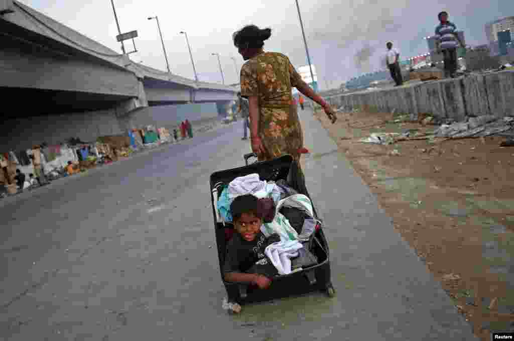 Three-year-old Riaz sits in an open suitcase filled with clothes as his mother wheels it along the side of a highway in Mumbai, India.