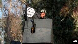 Un soldado de las fuerzas antiterroristas de élite de Irak, a bordo de un vehículo blindado, festeja sosteniendo una bandera del grupo extremista Estado Islámico abatido, durante la recuperación de la Universidad de Mosul.