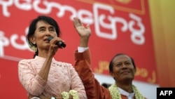 Burma's Aung San Suu Kyi, left, gives her speech beside a candidate for the National League for Democracy party in Yangon.
