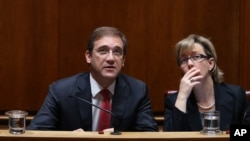 Portuguese Prime Minister Pedro Passos Coelho and Finance Minister Maria Luis Albuquerque, right, look at a wall clock during the debate of the government's four-year policy program at the Parliament in Lisbon, Nov. 10, 2015.