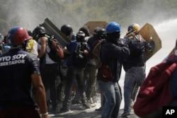 Manifestantes se enfrentan a la policía anti-disturbios en Caracas, Venezuela, cuando intentan marchar hacia la oficina del Defensor del Pueblo. Mayo 29, 2017.