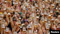 Para pengunjung meluapkan kegembiraan mereka setelah mendapatkan bir pertama mereka di gelas tradisional 'Masskrug' berukuran satu liter, di pembukaan Oktoberfest di Theresienwiese, Munich, Jerman (22/9).