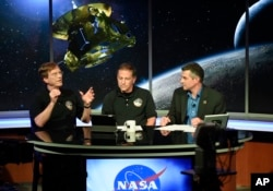 New Horizons Scientist Hal Weaver, left, talks with Mark Holdridge, center, and Mike Buckley as they await information from from the New Horizons spacecraft as it passes Pluto, July 14, 2015, in Laurel, Md.