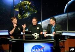 ນັກວິທະຍາສາດ ຂອງຍານ New Horizons ທ່ານ Hal Weaver (ຊ້າຍ) ສົນທະນາ ກັບ ທ່ານ Mark Holdridge (ກາງ) ແລະ ທ່ານ Mike Buckley ພວກເຂົາເຈົ້າ ລໍຖ້າຂໍ້ມູນ ຈາກ ຍານອະວະກາດ New Horizons ໃນຂະນະທີ່ຈະບິນຜ່ານ Pluto, ວັນທີ 14 ກໍລະກົດ 2015, ໃນ Laurel, ລັດ Maryland.