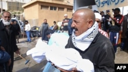 Bingazi'de bir hastane dışında ceset parçaları taşıyan bir Libyalı (AP Photo/Alaguri)