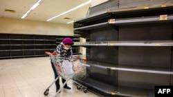 2020年2月6日戴著防護口罩的購物者在香港超市被全部賣空的貨架旁。