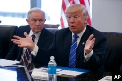 FILE - Then-Senator Jeff Sessions listens at left as Republican presidential candidate Donald Trump speaks with advisers at Trump Tower in New York, Oct. 7, 2016.