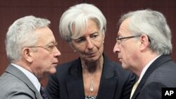 Italy's FM Tremonti and French counterpart Lagarde listen to Luxembourg's PM and Eurogroup chairman Juncker during a meeting in Brussels, May 16, 2011