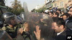 Iranian policemen prevent protesters from attacking the British Embassy in Tehran, during an anti-British demonstration, 04 Nov 2010