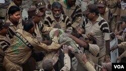 Regu penolong menarik badan seorang anak kecil dari sebuah apartemen yang ambruk di kawasan Taman Lalita, New Delhi.