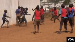 Children pass the time by playing intense soccer matches between the tents.