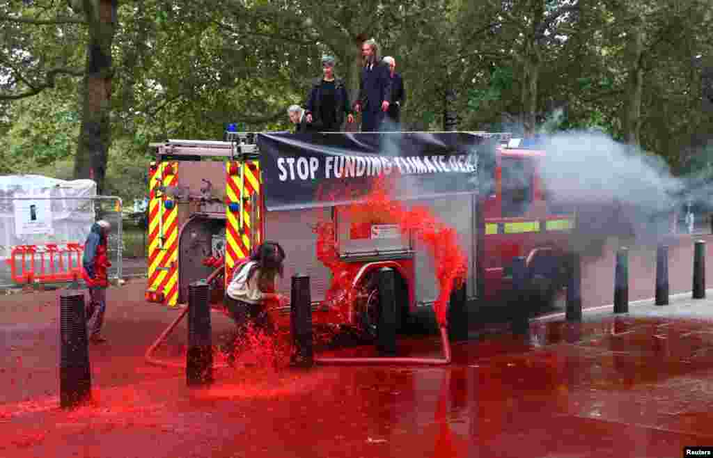 Climate activists from Extinction Rebellion spray fake blood outside the Treasury building in London, to draw attention to global climate breakdown.