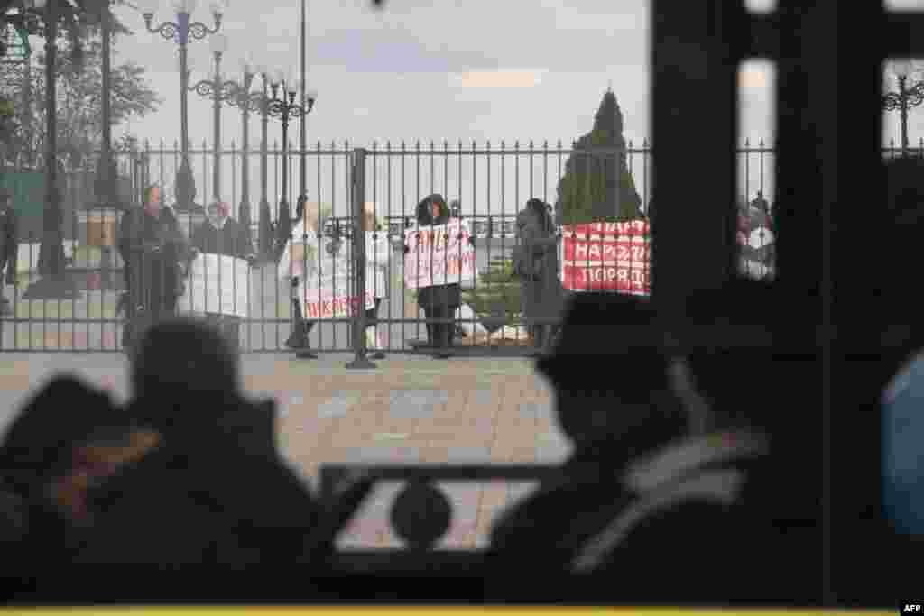Пассажиры рейсового автобуса не обращают внимания на митинг под Верховной Радой