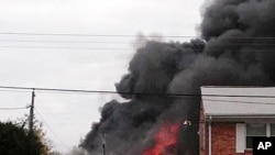 Smoke billows near an apartment complex where a Navy jet crashed in Virginia Beach, Virginia, March 6, 2012.
