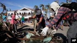 11月25日,菲律賓受颱風影響的災民和志願工作人員努力進行災後復原工作。