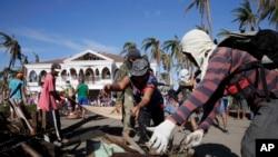 Các nạn nhân bão và những người tình nguyện bắt đầu dọn dẹp những đống đổ nát trong thành phố bị bão tàn phá Tacloban, ở miền trung Philippines, 25/11/13