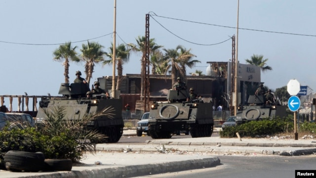 Lebanese Army soldiers on armored vehicles move towards an area of clashes in Sidon, southern Lebanon, June 23, 2013.