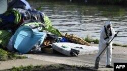 Un ouvrier nettoie le camp de fortune des migrants du Millénaire le long du canal de Saint-Denis près de la porte de la Villette, au nord de Paris, suite à son évacuation le 30 mai 2018.