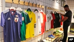 In this June 5, 2018 photo a customer looks at different national soccer team jerseys that are on display at a shop in London. With just days to go before the FIFA World Cup, some winners and losers have emerged among the often wild and wacky team jerseys
